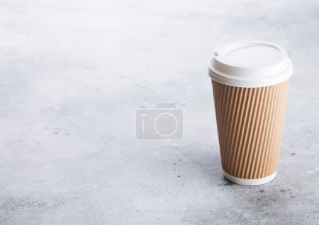Photo for Coffee cardboard cup for take away or coffee to go on stone kitchen background. Brown color. Space for text. - Royalty Free Image