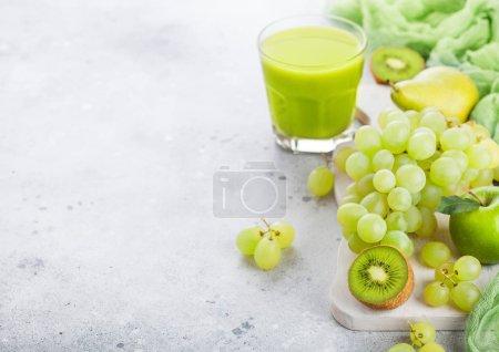 Photo pour Verre vert organique frais smoothie tonique fruits blanc planche à découper sur fond de pierre. Poires et raisins au kiwi et citron vert et pomme. - image libre de droit