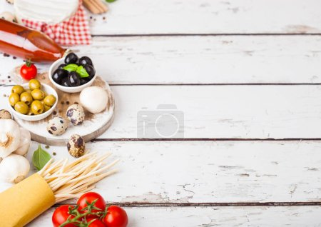 Photo for Homemade spaghetti pasta with quail eggs with bottle of tomato sauce and cheese on wood background. Classic italian village food. Garlic, champignons, black and green olives - Royalty Free Image