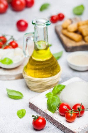 Photo for Fresh Mozzarella cheese on vintage chopping board with tomatoes and basil leaf with olive oil and tray with cheese sticks on stone kitchen background. - Royalty Free Image