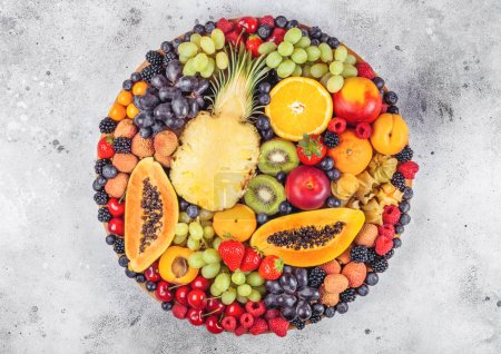 Photo for Fresh raw organic summer berries and exotic fruits in round large tray on light kitchen background. Papaya, grapes, nectarine, orange, raspberry, kiwi, strawberry, lychees, cherry. Top view - Royalty Free Image