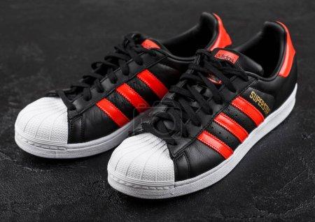Photo pour LONDRES, Royaume-Uni - 05 JUIN 2019 : Adidas Originals Superstar chaussures noires à rayures rouges sur fond noir . - image libre de droit