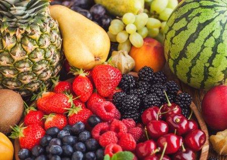 Photo pour Des baies d'été bio fraîches se mélangent dans un plateau en bois et des fruits exotiques sur fond en bois. Framboises, fraises, bleuets, mûres et cerises. Pastèque, poire, ananas, raisin. Vue du dessus - image libre de droit