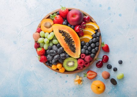 Photo for Fresh raw organic summer berries and exotic fruits in round wooden plate on blue kitchen background. Papaya, grapes, nectarine, orange, raspberry, kiwi, strawberry, lychees, cherry. Top view - Royalty Free Image