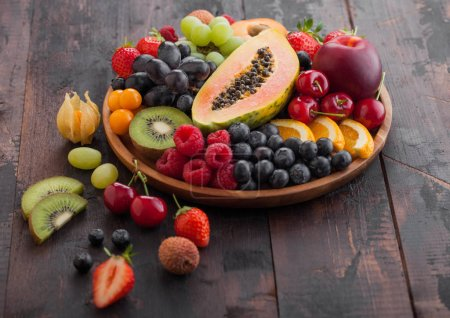 Photo pour Fruits exotiques et baies d'été biologiques crues fraîches dans une assiette ronde en bois sur fond de cuisine en bois foncé. Papaye, raisin, nectarine, orange, framboise, kiwi, fraise, litchi, cerise. Vue du dessus - image libre de droit
