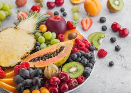 Foto de Frescas bayas de verano orgánicas crudas y frutas exóticas en plato blanco sobre fondo claro. Piña, papaya, uvas, nectarina, naranja, albaricoque, kiwi, pera, lichis, cereza y physalis. Vista superior - Imagen libre de derechos