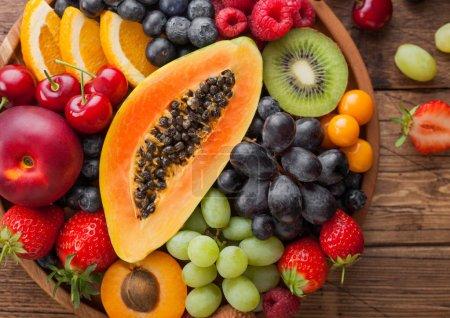 Photo pour Fruits exotiques et baies fraîches crues d'été biologiques dans une assiette ronde en bois sur fond de cuisine en bois. Papaye, raisin, nectarine, orange, framboise, kiwi, fraise, litchi, cerise.Vue de dessus - image libre de droit