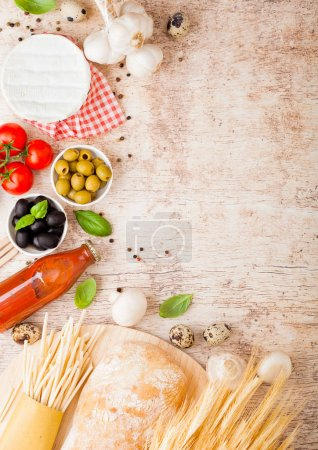 Photo for Homemade spaghetti pasta with quail eggs with bottle of tomato sauce and cheese on wood background. Classic italian village food. Garlic, champignons, black and green olives, oil and bread. - Royalty Free Image
