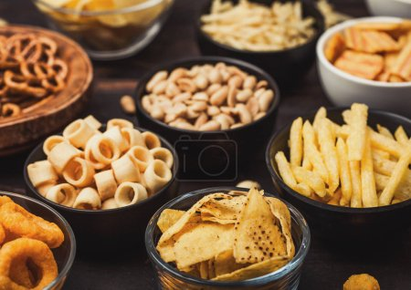 Photo for All classic potato snacks with peanuts, popcorn and onion rings and salted pretzels in bowl plates on wood. Twirls with sticks and potato chips and crisps with nachos and cheese balls. - Royalty Free Image