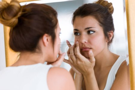 Portrait of beautiful young woman removing pimple from her face in a bathroom home.