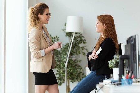 Aufnahme von zwei hübschen jungen Geschäftsfrauen, die sich einen Moment entspannen, während sie Kaffee im Büro trinken.