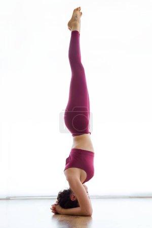 Shot of pretty young woman practicing yoga at home. Salamba Sirsasana pose.