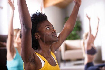 Tourné de groupe de jolies jeunes femmes sportives pratiquant le yoga à la maison