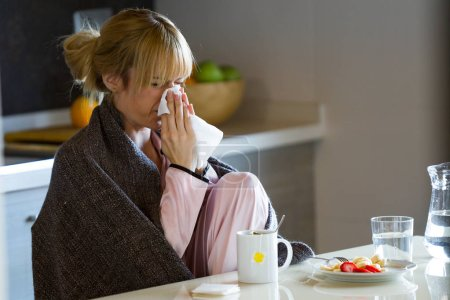 Shot of illness young woman sneezing in a tissue at home.