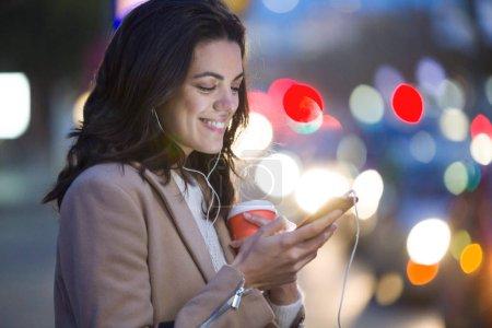 Photo pour Coup de jeune et jolie femme à l'aide de son téléphone portable tout en tenant la tasse de café dans la rue pendant la nuit. - image libre de droit
