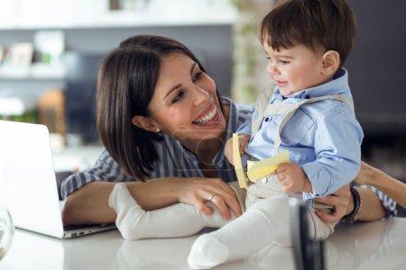 Photo pour Tourné de jolie jeune mère avec son bébé jouant avec un cahier à la maison . - image libre de droit