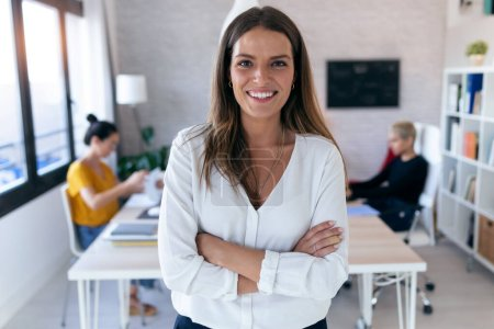 Photo for Portrait of pretty young businesswoman looking at camera. In the background, her colleagues working in the office. - Royalty Free Image