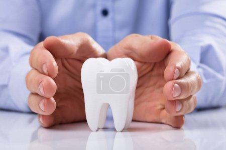 Photo pour Main d'homme protégeant la dent blanche hygiénique saine sur la table réfléchissante - image libre de droit