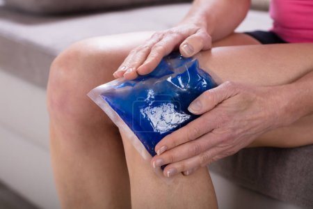 Close-up Of A Woman Applying Cool Gel Pack On Her Knee