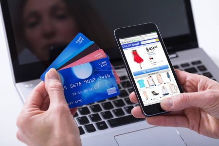 Close-up Of A Woman Shopping Online With Credit Cards On Mobile Phone Against Laptop