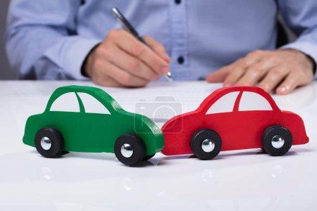 Photo pour Gros plan de la voiture rouge et verte en face de l'homme d'affaires travaillant sur le Document - image libre de droit