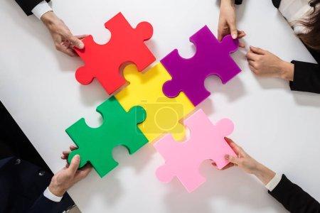 Gruppe von Geschäftsleuten löst buntes Puzzle auf Schreibtisch