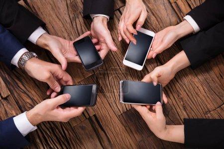 Photo pour Vue élevée des hommes d'affaires utilisant le téléphone portable sur un bureau en bois - image libre de droit