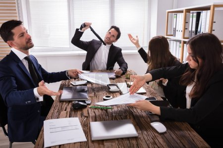 Group Of Frustrated Young Businesspeople Having Discussion In Meeting