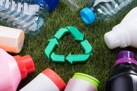 High Angle View Of Green Recycle Symbol Surrounded With Water Bottles On Grass