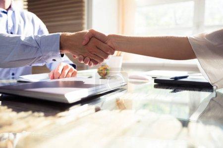 Foto de Primer plano de dos socios de negocios que estrechan las manos sobre el escritorio en la oficina - Imagen libre de derechos