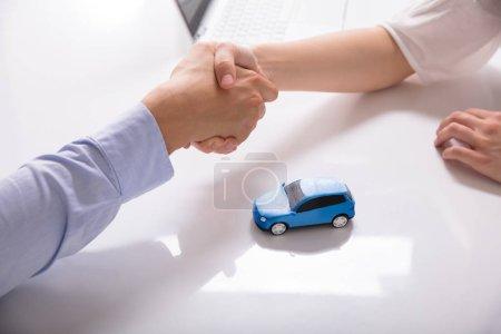 Photo pour Concessionnaire automobile, serrant la main de son Client en dehors de la petite voiture bleue - image libre de droit