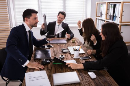 Businesspeople Blaming Depressed Young Male Colleague At Workplace