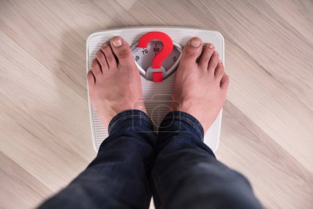 Person's Feet Standing On Weight Scale With Red Question Mark Sign
