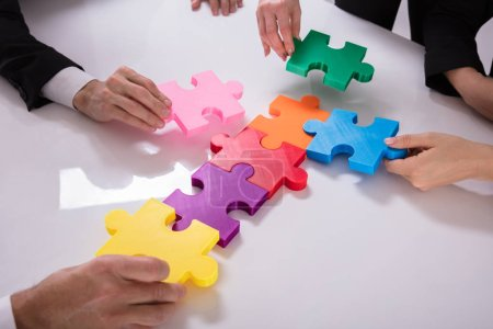 Photo for Group Of Businesspeople Solving Multi Colored Jigsaw Puzzle On Desk - Royalty Free Image