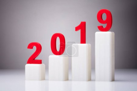 Year 2019 With Increasing Arrow Against Gray Background