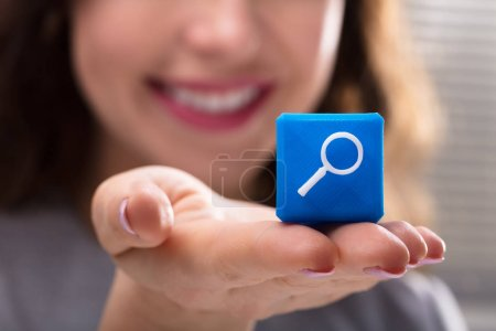 Photo for Close-up Of Woman's Hand Holding Blue Cubic Block With Magnifying Glass Icon - Royalty Free Image