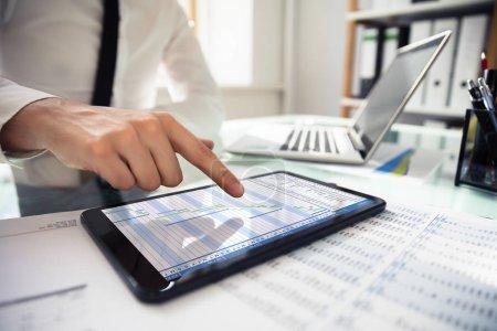 Photo pour Gros plan de la main d'un homme d'affaires analysant Gantt Chat sur tablette numérique sur le lieu de travail - image libre de droit