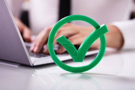 Photo pour Gros plan sur la coche verte marque signe en face de l'homme d'affaires à l'aide d'ordinateur portable - image libre de droit