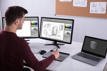 Side View Of Designer Drawing Suitcase On Computer Using Graphic Tablet In Office