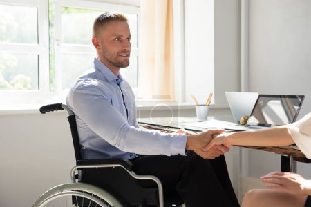 Happy Disabled Businessman Sitting On Wheelchair Shaking Hand With His Partner