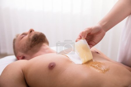 Man Waxing Chest With Wax Strip In Spa
