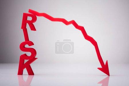 Photo pour Mot à risque rouge avec flèche déclinante sur fond réfléchissant - image libre de droit