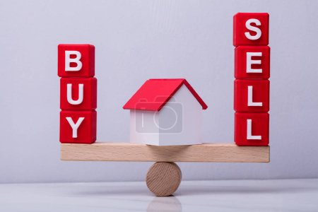 House Model Between The Red Cubes With Buy And Sell Text Balancing On Seesaw