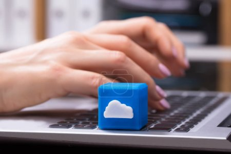 Human Hand Using Laptop With Cubic Block Showing Cloud Symbol