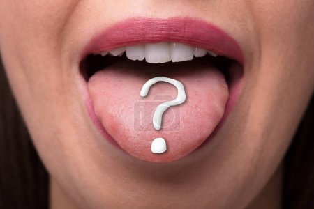 Close-up Of A Woman's Tongue With White Question Mark Sign