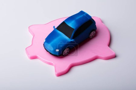 Small Blue Car Over Flat Pink Piggybank Isolated On White Background