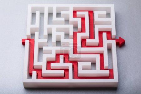 Photo pour Vue à angle élevé de flèche rouge montrant le chemin à travers le labyrinthe - image libre de droit