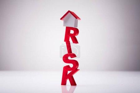Small House Model Over Risk Word Against White Background