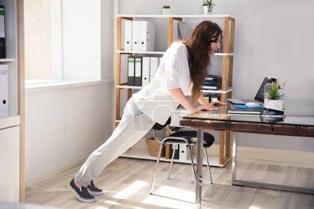 Photo pour Vue de côté d'une jeune femme d'affaires faisant pousser sur le lieu de travail - image libre de droit