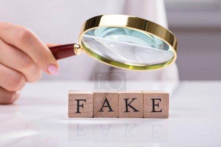 Photo pour Gros plan de la main d'une femme d'affaires examinant des blocs en bois montrant un faux mot - image libre de droit